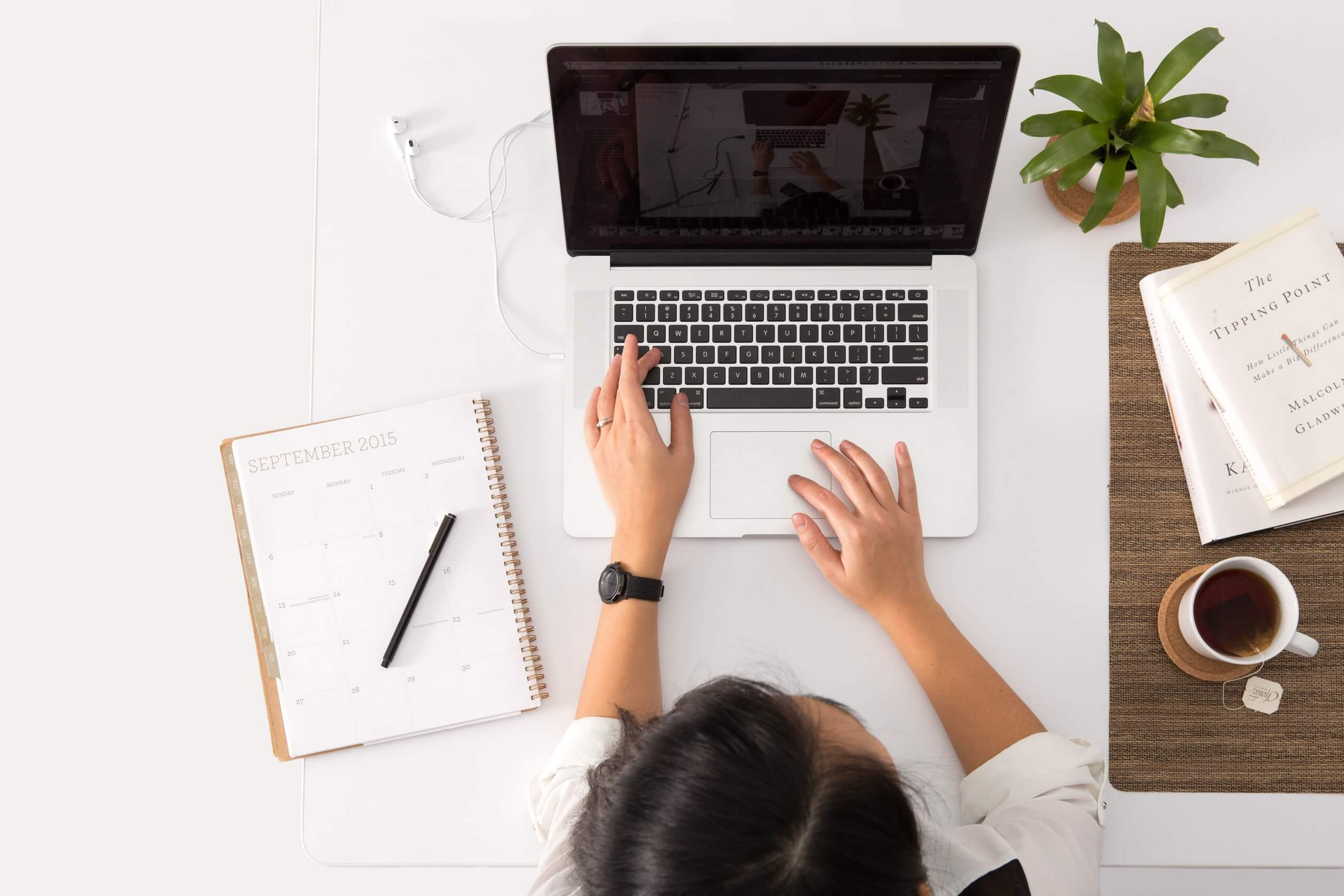 Image of a woman using a laptop on a white desk.