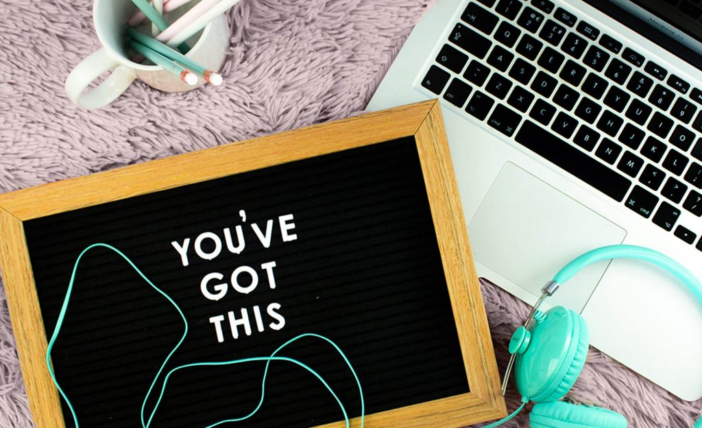 """Image of a sign that says """"You've got this"""" sitting next to a laptop"""