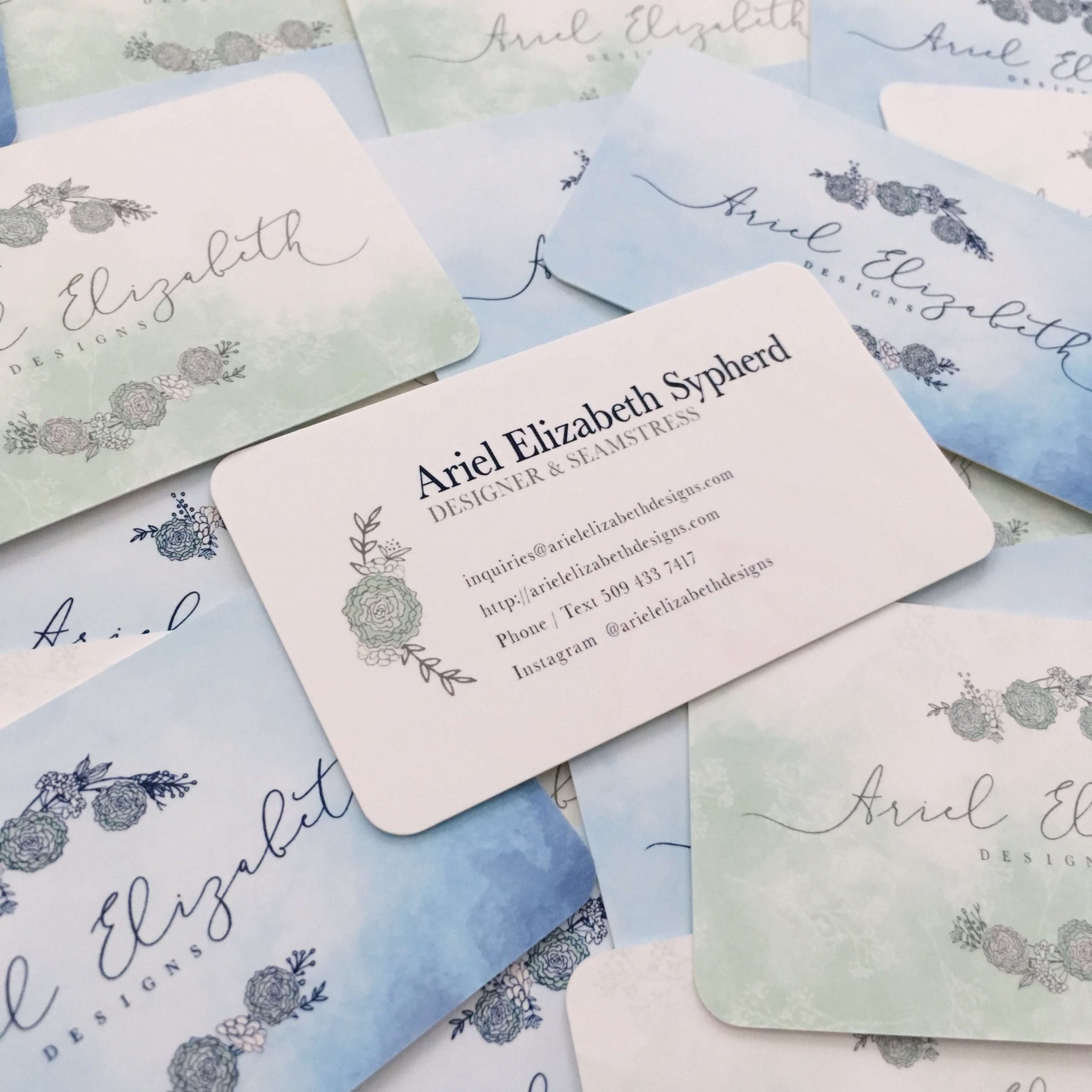 Actual business cards for Ariel Elizabeth Designs, featuring two different back sides in different colors, and the front side with Ariel's information.