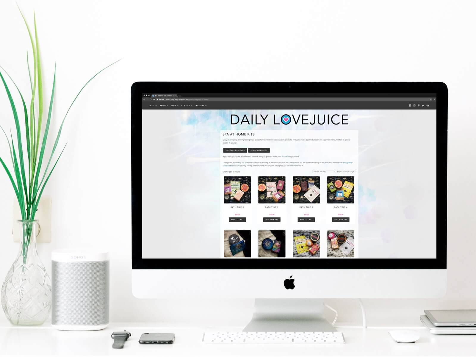 iMac on a desktop. The screen is showcasing the Daily Lovejuice website, open on their Shop page and showcasing their self care products.