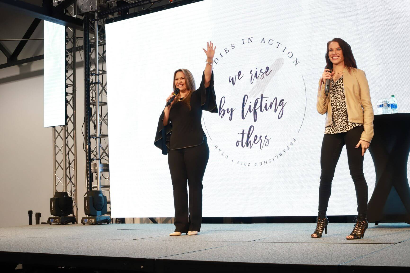 Photo of Ladies in Action organizers Dora Lopez and Diana Groesbeck, in front of a giant screen showcasing the Ladies in Action logo.