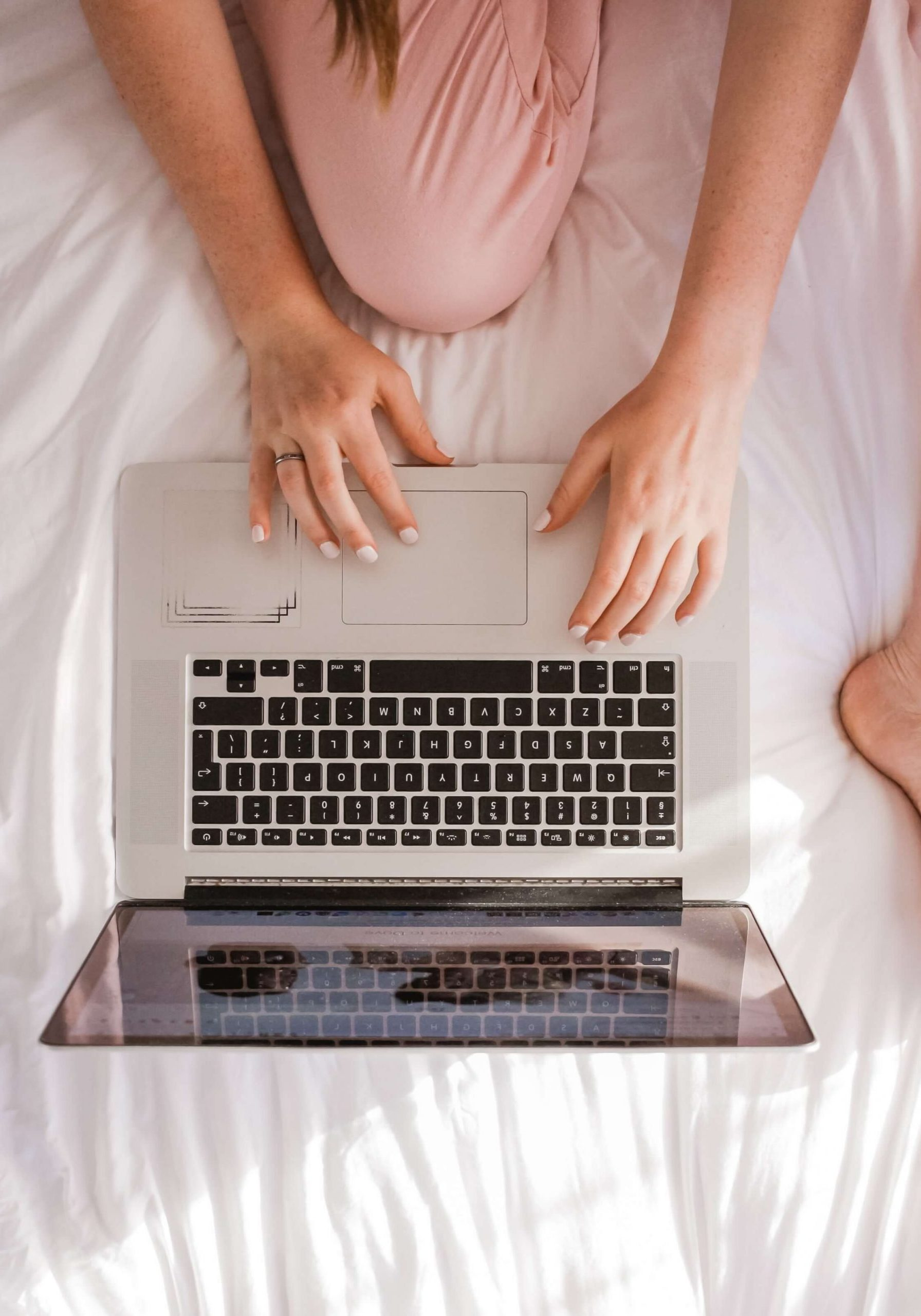 Image of a Woman sitting on a bed using her laptop